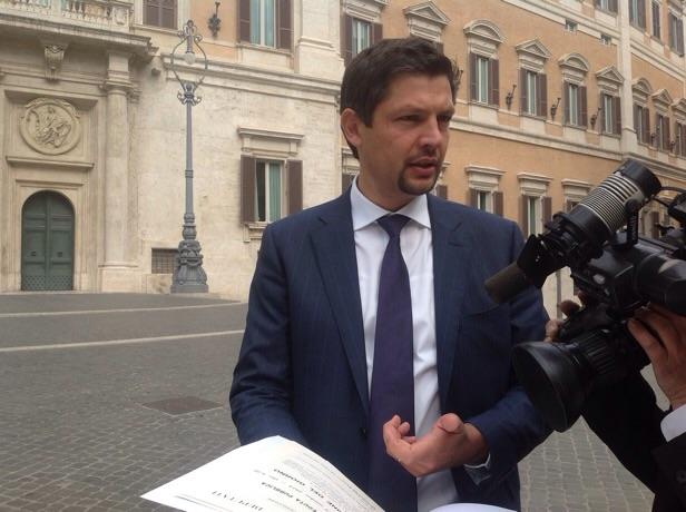 """SVP-Fraktionssprecher Daniel Alfreider vor der Abgeordnetenkammer mit dem Text """"sblocca Italia"""" (Foto: Sonja Schiefer)"""