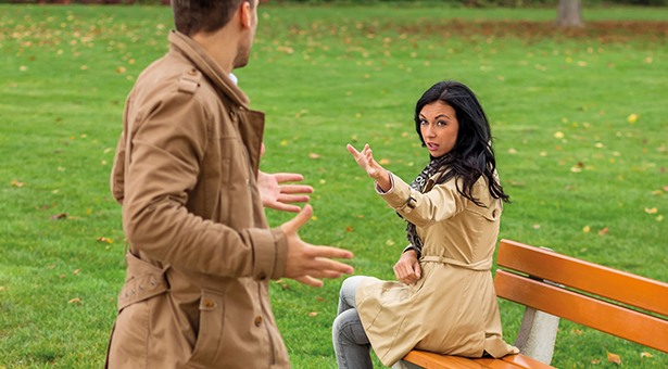 34088125 - a young couple sitting on a park bench and fight